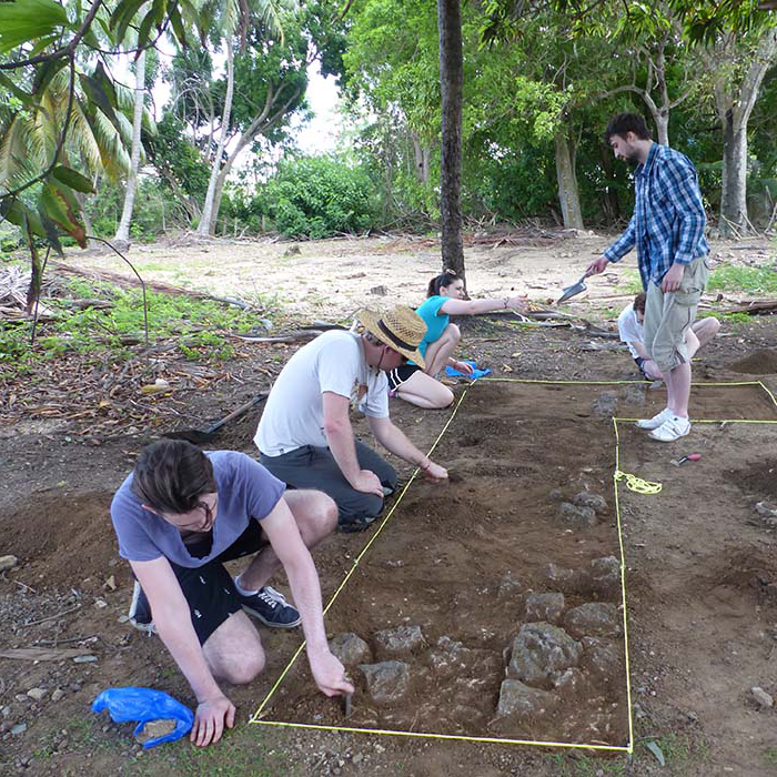 Four students excavating earth in rectangle marked out by string